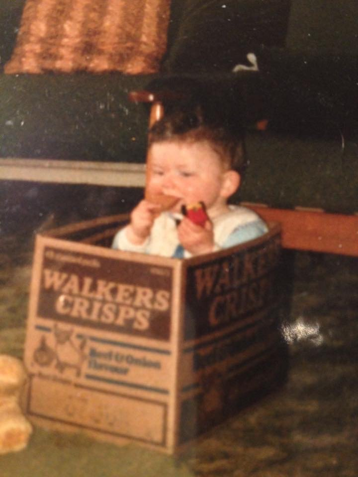 Small child eating biscuits in a Walkers Crisp box